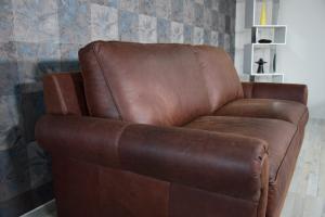 FLORES Divano 3 posti in pelle color cuoio con borchie con base e piedini in legno, cuscini in piume d'oca e inserto in memory – Design vintage