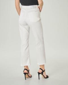 Jeans bianchi a trombetta in cotone stretch con orli sfrangiati