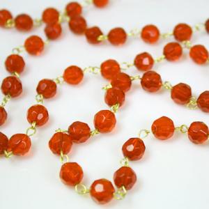 Catena 100 cm perle Ø 10 mm sfaccettate cristallo arancione, spillo a occhiello ottonato brillante.