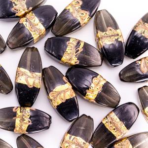 Perla di Murano a oliva 42 mm. Vetro nero in pasta vitrea e grigio trasparente con decori in oro e bronzo. Foro passante.