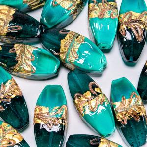 Perla di Murano a oliva 42 mm. Vetro verde in pasta vitrea e verde trasparente con decori in oro e bronzo. Foro passante.